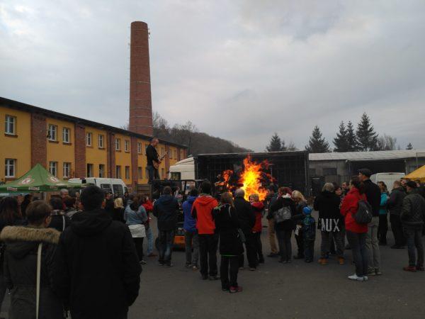 Płonie wcześniej przygotowane ognisko, w tle mieni się scena